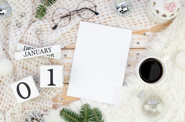 Беспорядочное рабочее место с чистым листом бумаги, кофейной чашкой и рождественскими украшениями
