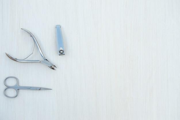 Металлические аксессуары для маникюра на белом деревянном фоне вид сверху плоская планировка