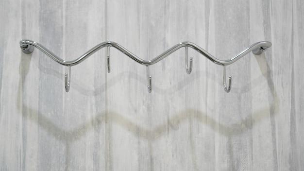 Металлические клейкие крючки на сером фоне. вешалки для полотенец