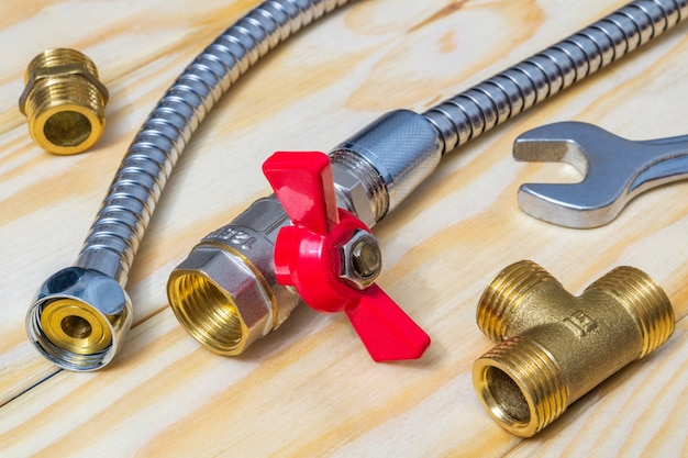 Metal ball valve with red handle with fittings and hose prepared for repair