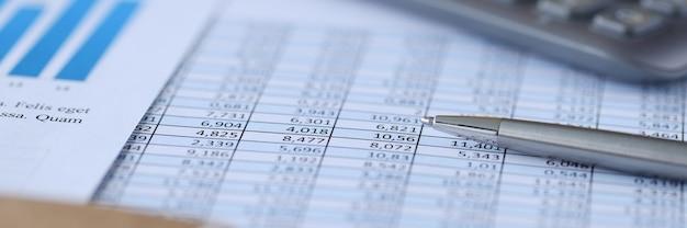 Металлическая шариковая ручка, лежащая на документах в цифрах на столе, бухгалтерский учет и статистика крупным планом