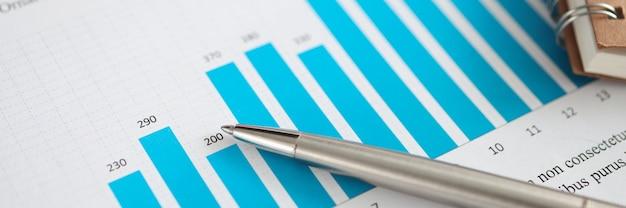 Металлическая шариковая ручка, лежащая на документах с концепцией бухгалтерского учета и статистики крупным планом