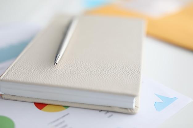 ノートブックに横たわっている金属製のボールペンとチャートや図のクローズアップとドキュメント