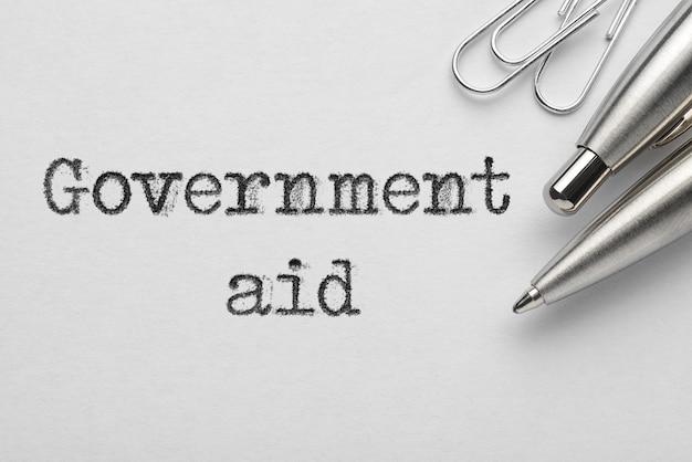 タイプライターで印刷された金属製のボールペン、ペーパークリップ、政府援助の言葉