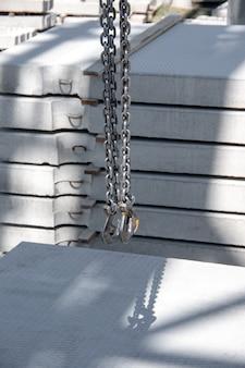 鉄筋コンクリート製品を背景にしたチェーン製スリングの金属棒。