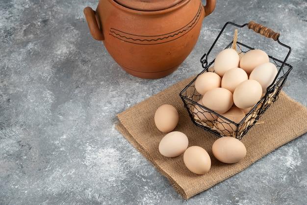 Cesto in metallo di uova di gallina crude e vaso antico sulla superficie in marmo.