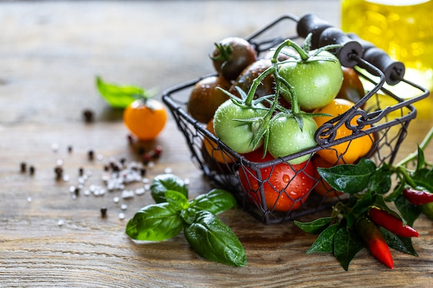 Metal basket with ripe different red, yellow and green tomatoes on a wooden table and basil leaves