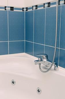 파란색 욕실에 긴 샤워 호스가 있는 금속 욕실 수도꼭지