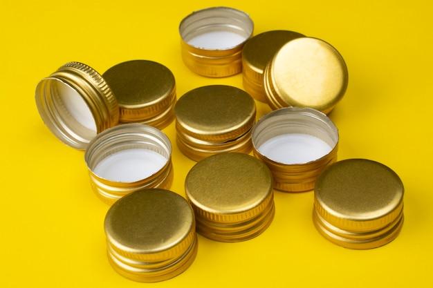 Металлические пробки для бутылок на желтом фоне