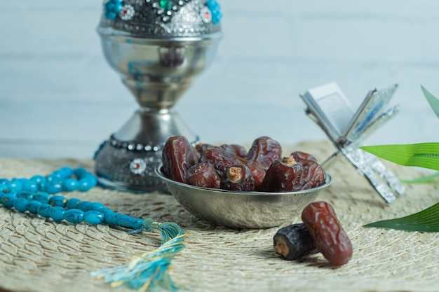 Metal bowl of delicious dates on wooden table.