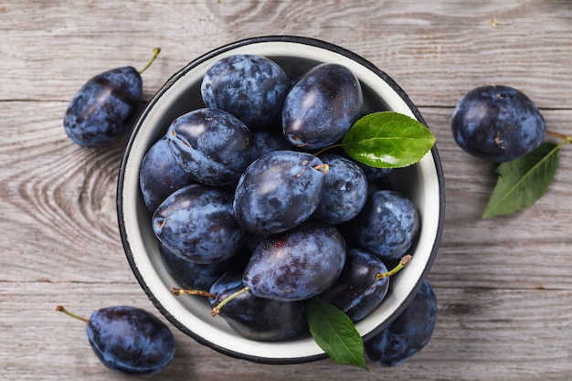 Metal bowl full of ripe prune fruit on a wooden table