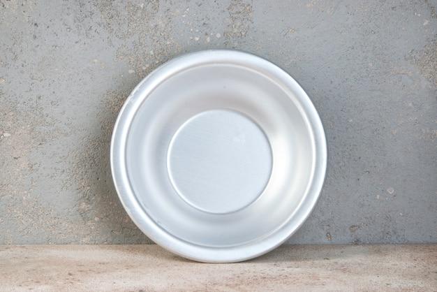 Металлическая чаша на бетонной поверхности Premium Фотографии