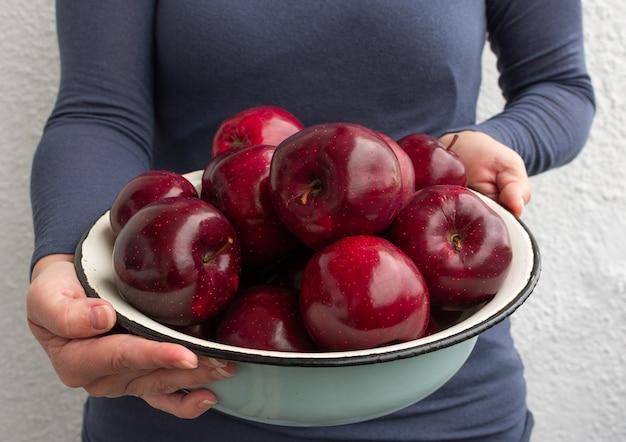 여성의 손에 신선한 빨간 사과, 여름 정원 사과와 금속 그릇