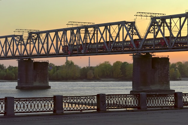Metal bridge with running train over the river ob  embankment in yellow evening light