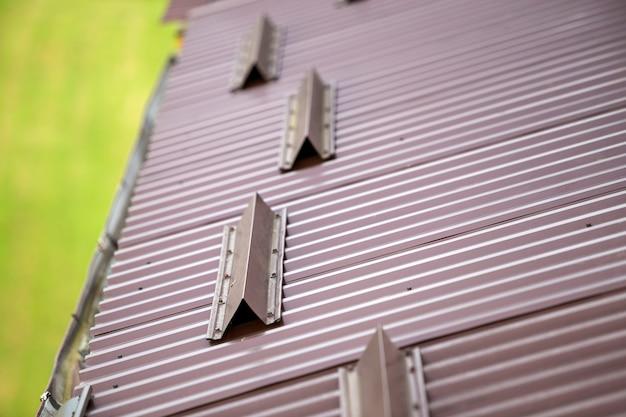 Металлическая коричневая черепица покрывает поверхность крыши дома, водосточную трубу и защитное ограждение.
