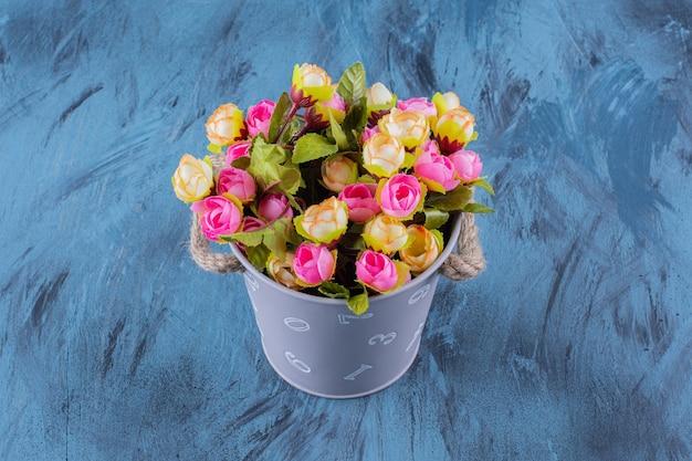 Secchio di metallo di disposizione dei fiori colorati sul blu.