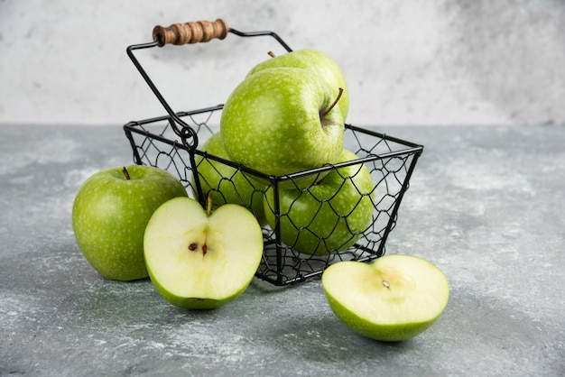 Secchio di metallo di mele verdi fresche sul tavolo di marmo.