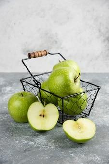 Metal bucket of fresh green apples on wooden board.
