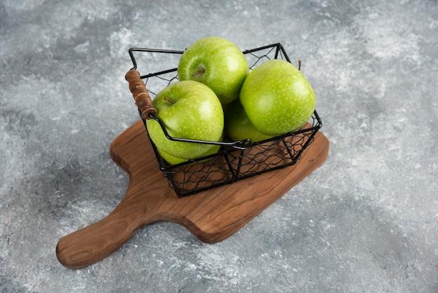 Secchio di metallo di mele verdi fresche su tavola di legno.