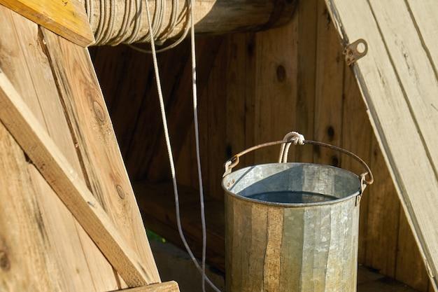 夏の日に田舎の古い木製のドローウェルから取ったばかりの真水でいっぱいの金属製のバケツ