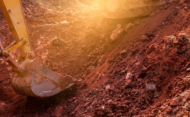 Металлический ковш экскаватора, копающего землю. экскаватор работает по копанию грунта на стройплощадке. экскаватор копает грунт. землеройная машина. экскаваторная машина. строительный бизнес.