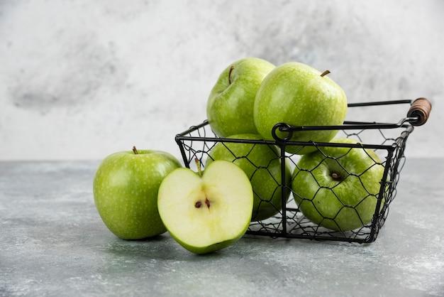 Металлическое ведро свежих зеленых яблок на мраморном столе.