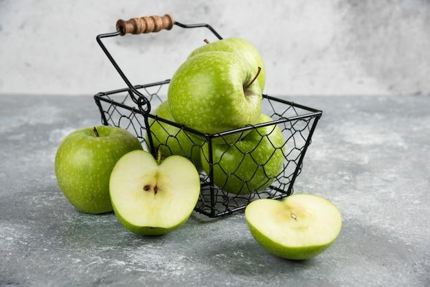 大理石のテーブルに新鮮な青リンゴの金属製のバケツ。