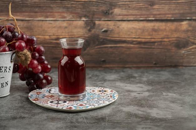 Металлическое ведро красного свежего винограда и стакан сока на мраморном столе.