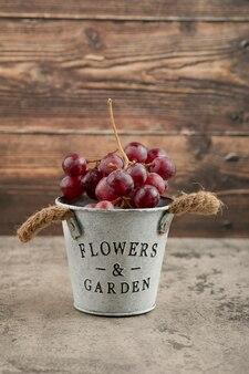 大理石のテーブルの上の赤い新鮮なブドウの金属製のバケツ。