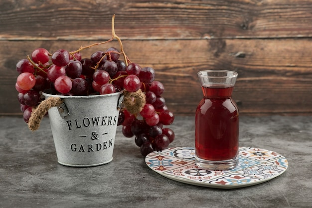 Metal bucket of red fresh grapes and glass of juice on marble table.