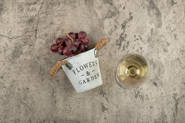 Metal bucket of red fresh grapes and glass of white wine on marble surface.