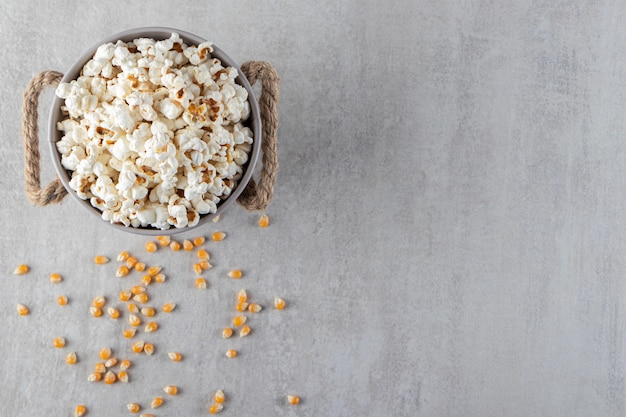 Metal bucket of salted popcorn placed on stone background.