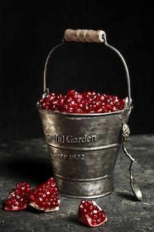 Металлическое ведро с ягодами граната.