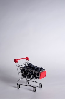 Metal cart with blueberries on a white background with a copy of the space. vertical orientation
