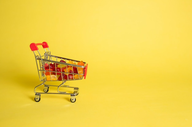Metal cart with marmalade in the shape of bears on a yellow isolated background with space for text