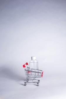 Металлическая тележка с прозрачной бутылкой на белом фоне с копией пространства