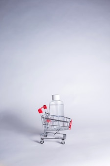 Metal cart with transparent bottle on white background with copy space