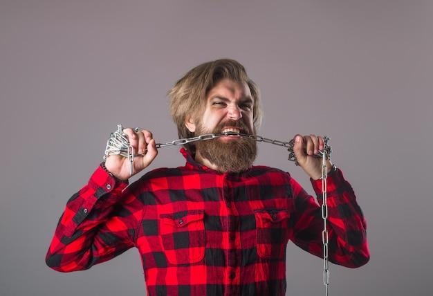 Металлическая цепочка. зависимость. концепция свободы. человек с металлической цепью. бородатый мужчина с цепью. раб. проблемы с людьми. прорыв.