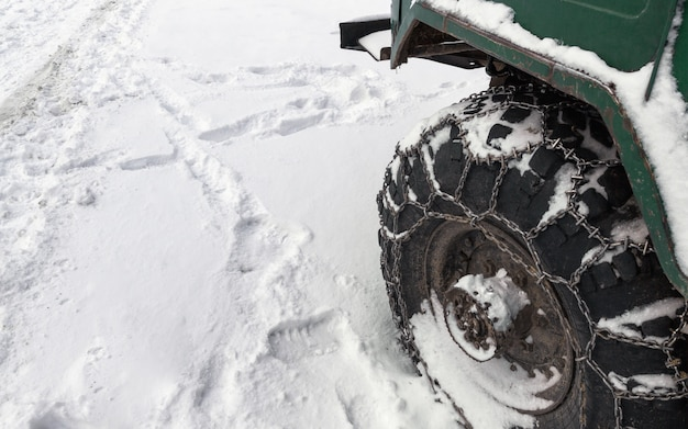 Metal chain on offroad truck tire in snowy road