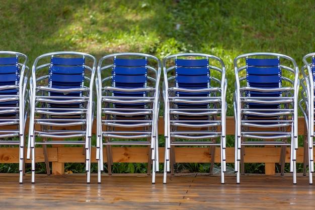 금속 의자가 쌓여 있고 거리 레스토랑, 카페 또는 레크리에이션 센터의 비치 파라솔 옆에 있습니다. 의자는 나무 바닥에 있습니다. 리조트는 관광객과 방문객을 기다리고 있습니다
