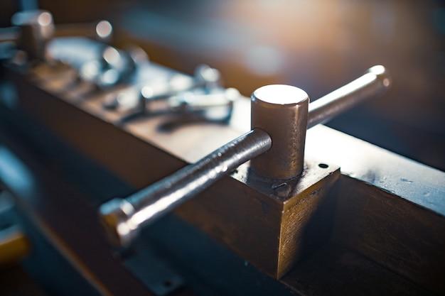 수동 유연한 대규모 기계의 금속 크롬 볼트 및 너트. 판금 강철 가공을 위한 오래된 고전적인 빈티지 복고풍 기계 부품 기계 건설 프레스