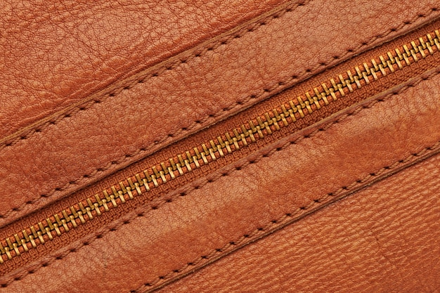 Metal closed zipper on brown leather bag