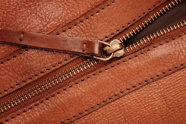Metal closed zipper on brown leather bag.