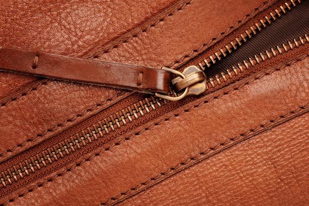 Металлическая закрытая молния на коричневой кожаной сумке.