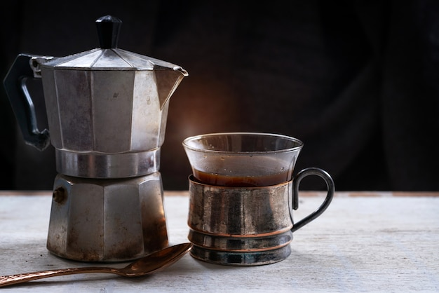 Metal coffee pot and black coffee in vintage cup, black background