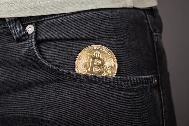 Металлическая монета биткойн в переднем кармане джинсов крупным планом.