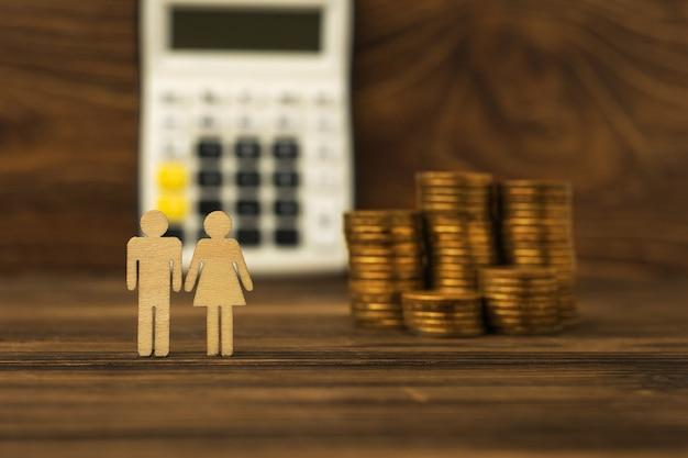 Металлические монеты, калькулятор, женские и мужские деревянные фигурки на деревянном фоне.