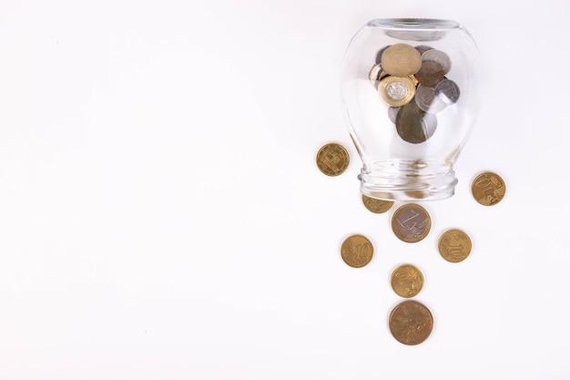 Металлические монеты выливаются из банки. скопируйте пространство.