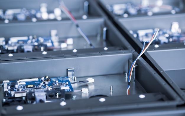 金属部品とマイクロ回路は、ビデオフルーツを備えた将来の強力なスーパーコンピューターのケースの製造中に金属コンパートメント上にあります。専用マイニングコンピュータのコンセプト制作