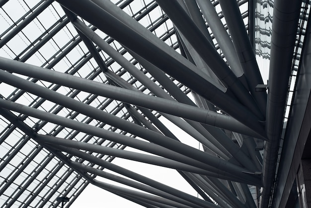 Metal construction. diagonal iron pipes holding the glass roof, close-up. cropped image. urban architecture